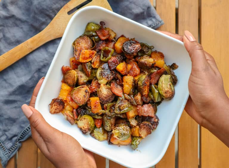 hands holding bowl of maple roasted brussels sprouts with bacon and butternut squash