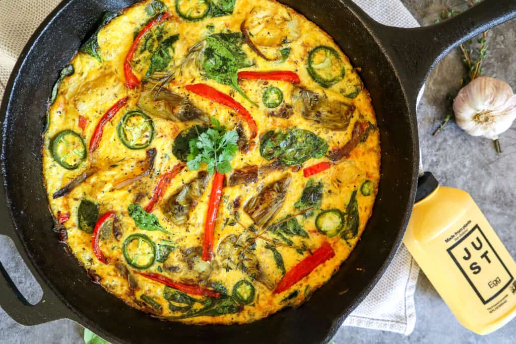 overhead shot of fully cooked vegan frittata with just egg, jalapenos, red peppers, spinach, and artichoke.
