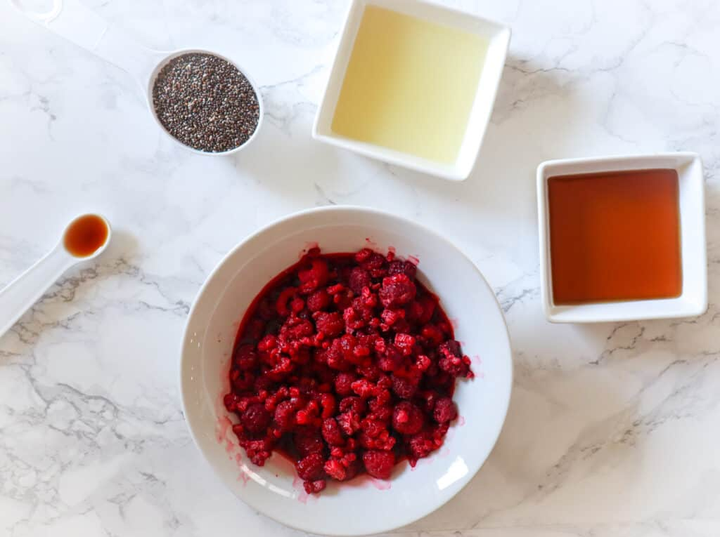 ingredients needed to make raspberry chia jam, frozen raspberries, chia seeds, lemon, maple syrup, vanilla