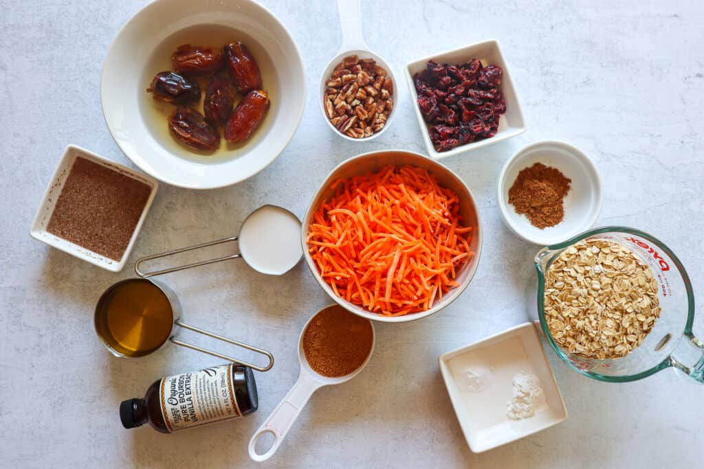 Ingredients to make Blender Carrot Cake Muffins: gluten free oats, cinnamon, nutmeg, shredded carrots, coconut sugar, non dairy milk, olive oil, pecans, dried cranberries, soaked pitted dates, flax egg, baking powder, baking sugar