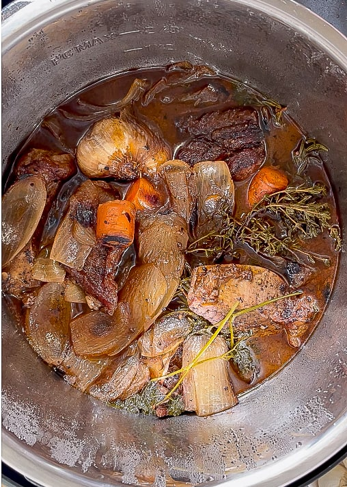 overhead image of short ribs carrots and onions cooked in an Instant Pot