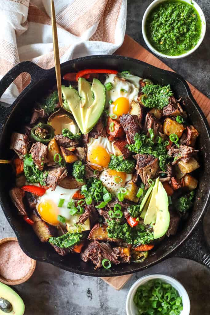 Image of beef short rib hash with sweet potatoes in a large cast iron skillet with baked eggs, topped with chimichurri, green onions, and avocado. ramekin with chimichurri in the top left corner, chopped green onions in the bottom right corner, a small bowl, and half of avocado in the bottom left corner.