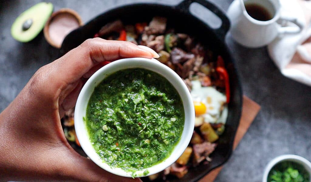 close up of chimichurri in a ramekin with short rib has in cast iron in the background