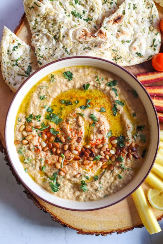 Baba ganoush recipe, close up of finished baba ganoush topped with pine nuts, parsley, olive oil, and served with pita bread, tomatoes, and carrots