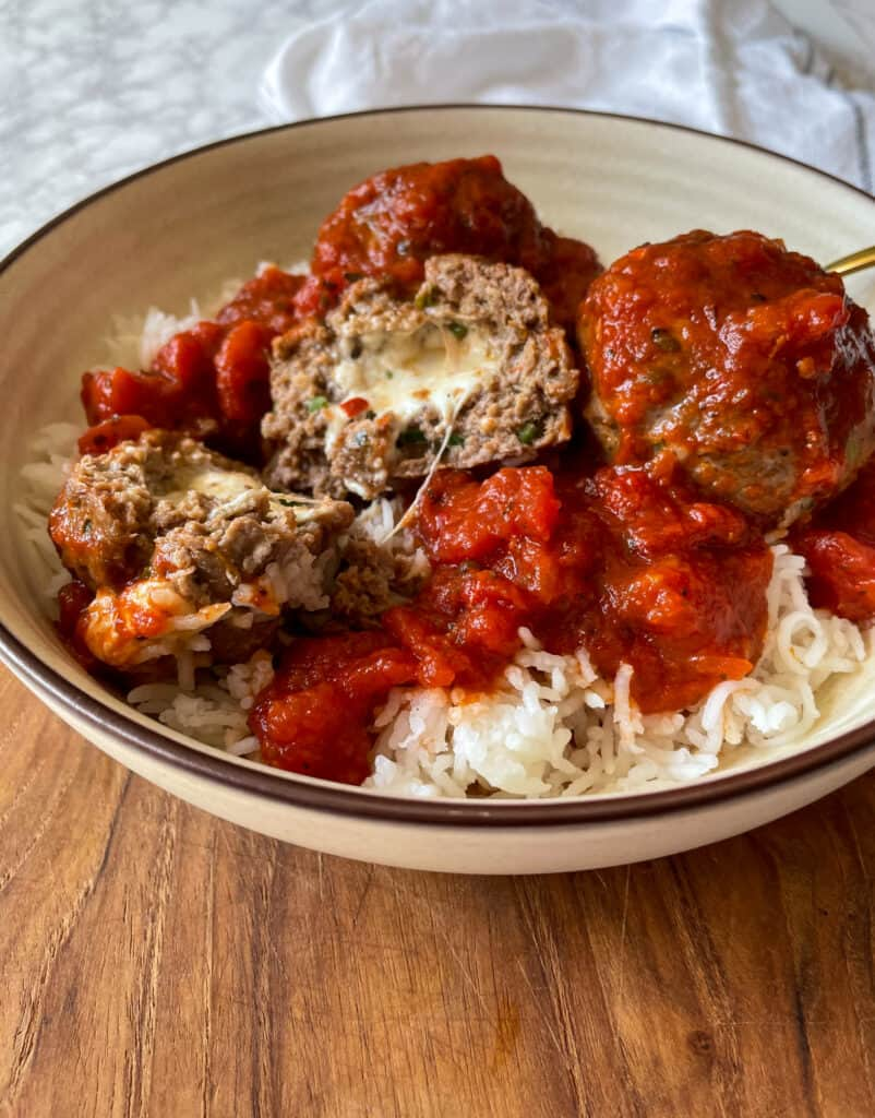 Air Fryer Cheese Stuffed Meatballs with Marinara Sauce served over rice